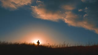 Silhouette of a man with a backpack against bright sky sunset. Sun goes down. Travel Concept. Tourist go travel nature outdoors lifestyle.