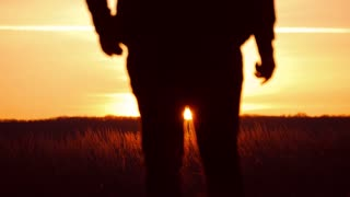 Silhouette of a man with hands raised in the sunset. Man with his arms wide open. Go to the sunset, the lower angle. A man is walking along the road against the sunset. Travelers concept.