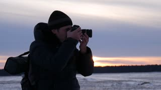Silhouette of a nature photographer, taking pictures at sunset