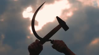 silhouette of a sickle and a hammer against the sky