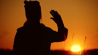 Silhouette of adorable baby girl at sunset, farewell to the sun.