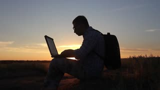 Silhouette of business man with laptop working on the field at sunset time. Concept freelancer, performing tasks, anger from failure and throwing a laptop.