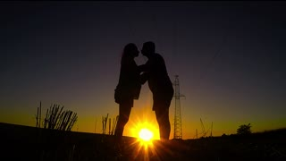 Silhouette of dad and pregnancy mom at sunset with beautiful nature background. Man kissing pregnant belly silhouette sunset.