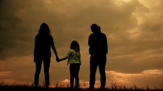 Silhouette of family walking together at sunset.