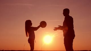 Silhouette of happy father and daughter who playing with the ball on the meadow at the sunset time. Concept of friendly family.