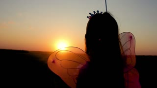 Silhouette of happy little girl dressed in a fairy costume with wings. The child presents himself as a sorceress, the concept of children's play and imagination.