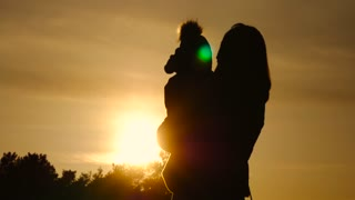 Silhouette of happy mother and little son play at sunset.