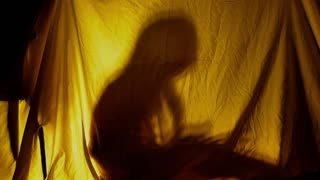 Silhouette of little girl reading a book inside a blanket fort in the evening, lit by a lamp from inside.