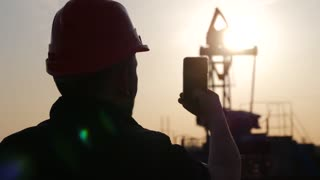 Silhouette of man engineer with phone overseeing the site of crude oil production at sunset.