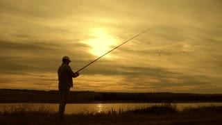 Silhouette of man enjoying fishing with beautiful sunset.