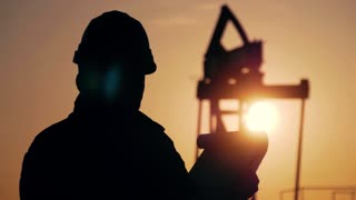 Silhouette of oilfield worker at crude oil pump in the oilfield at golden sunset. Industry, oilfield, people and development concept.