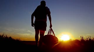 Silhouette of the people with a shoulder bag to see the sun Sky background. Man standing on the mountain with his arms wide open.