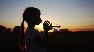 Silhouette of young girl drinking water from bottle in wheat field at sunset in summertime. Rehydrate your body.