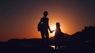Silhouettes of mother and child tourists hiking at sunset. Mom and daughter on summer vacation carrying backpacks. Little girl following her mom on cliff edge. The concept of traveling with children.