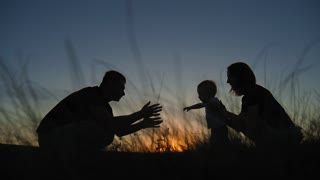 Silhouettes of mother and father teaching their baby boy how to walk. silhouette family kid learns to walk