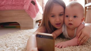 Sister taking selfie on the phone with a little brother