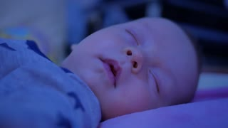 Sleeping newborn baby in bed. Smiling in a dream, a beautiful little boy is sleeping sweetly.
