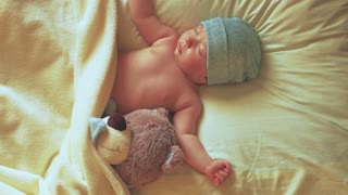 sleeping newborn baby on with a teddy