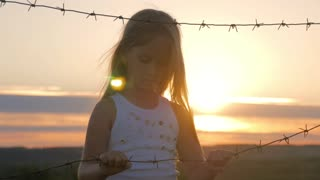 Small girl is at sunset behind barbed wire. Child hands holding the wire. The concept of freedom and Immigration.