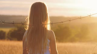 Small girl is at sunset behind barbed wire. The concept of freedom and Immigration.