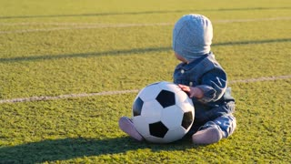 Smiling baby boy with a soccer ball at football field. Portrait of a little child sitting at stadium with a ball. Future football star. Football training concept.