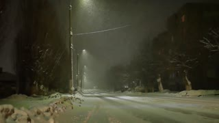 Snow falls against the background of a lamppost at night. Night winter street lamp with falling snow.