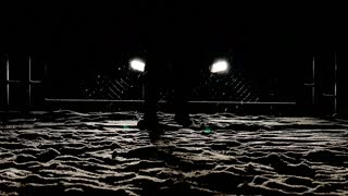 Snow falls in the headlights, walking feet into dark night shot in slow motion. mystery person background.