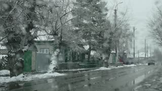 Snow falls on the road, traffic of cars, poor visibility.