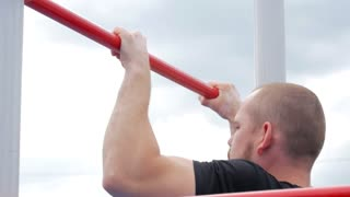 Strong young man making pull ups exercises. Close up of strong athlete doing pull-up on horizontal bar outdoors. Sport lifestyle.