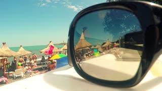Sunglasses over the beach background, sea landscape reflecting in the sunglasses on the beach.