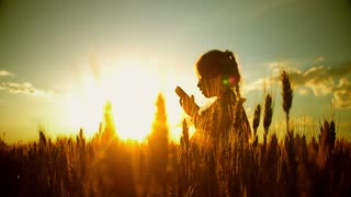 Sunrise or sunset, stylish beautiful the girl with the phone standing back and raised his hands up and rejoice against the bright sky and Golden fields.