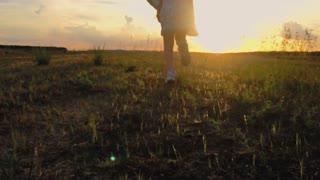 Sunset back shot of cute teenager girl wears dress runing on green meadow. 120 fps, slowmotion.