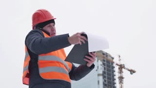 Supervisor reading clipboard while using mobile phone at construction site.