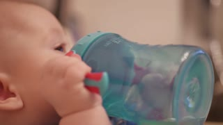 Sweet baby holding bottle and drinking water.