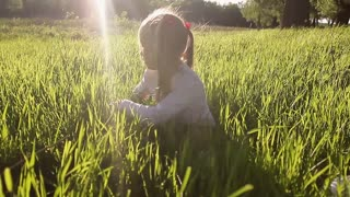 Sweet beautiful girl sitting on a green meadow. Beautiful Spring Young Girl Outdoors Enjoying Nature. Healthy Smiling Girl in Green Grass. Spring Meadow. Play the ball.