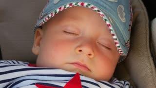 Sweet little baby boy sleeping in stroller