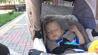 Sweet little baby boy sleeping in stroller.
