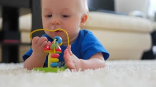 Sweet small baby playing with toys on a white carpet at home. Little baby boy with a toy lying on the floor at home.
