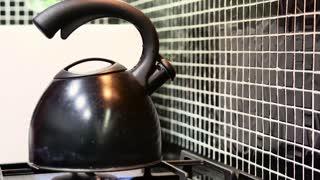 Tea kettle boils on gas stove