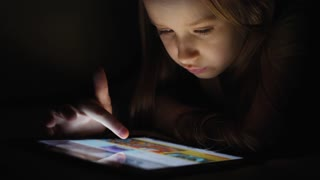 Teen girl looks into the tablet pc in the dark with light reflection on his face.