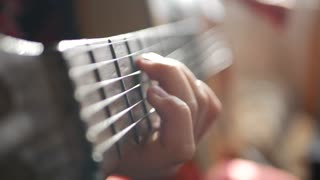 Teen girl playing guitar at home. Close up of cute teen indoors in a hoody softly strumming her guitar.