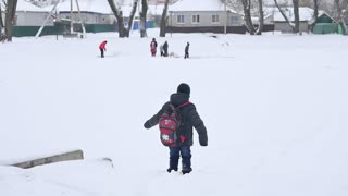 The boy runs through the snow. A child with a backpack runs. Winter fun.