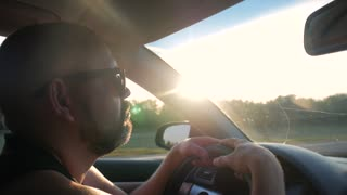 The driver driving the car rides along the road, the bright rays of the sun shine. Profile of young handsome man drives a car at sunset. Summer time. Close-up.