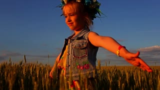 The girl in a dress and a wreath of flowers and greenery stands in a field on a background of sunset sky