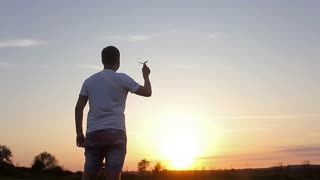 The man hold paper airplane and launch on the background of picturesque sunset. Young man launch paper plane during sunset with sun flare as in childhood.