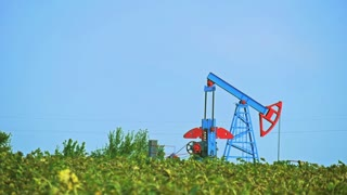 The oil pump, industrial equipment. Operating oil and gas well in European oil field, profiled on blue sky with cumulus clouds.