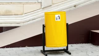 The public yellow recycling bin on the ground.