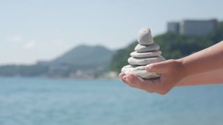 The pyramid of stones lies on the children hand against the background of the blue sea.