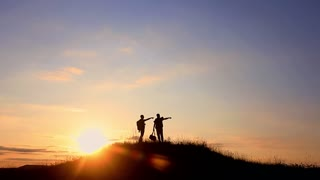 The Silhouette of two man standing on the top of mountain with Backpacks and other Gear expressing Energy and Happiness. Travel concept.