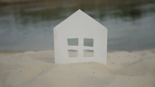 The symbol of the house standing on the rivershore.